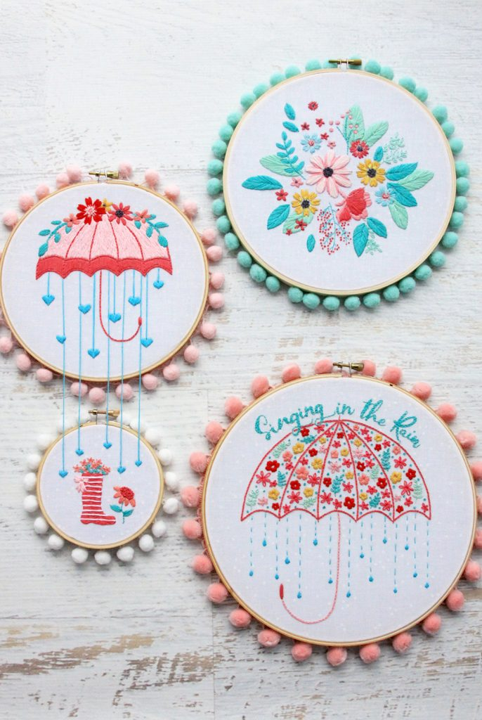 Four embroidery hoops with embroidered flowers, umbrella, rain boot with flowers.