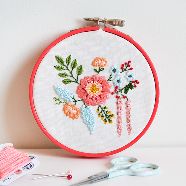 Embroidery hoop with embroidered floral bouquet, embroidery thread and small scissors