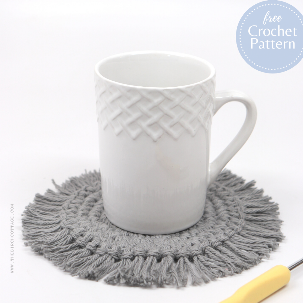 Coffee cup with crocheted coaster with fringe