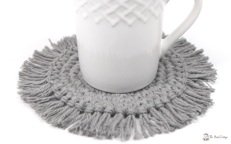 Coffee cup with crocheted coaster with fringe.