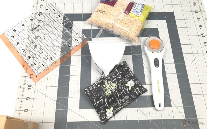 ruler, funnel, rotary cutter and mat, rice and fabric