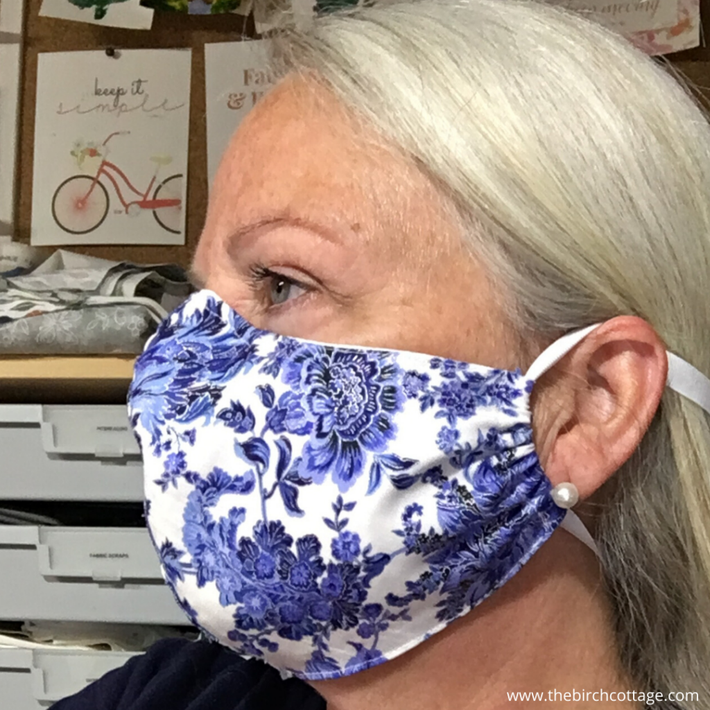 Pam wearing a fitted blue and white face mask